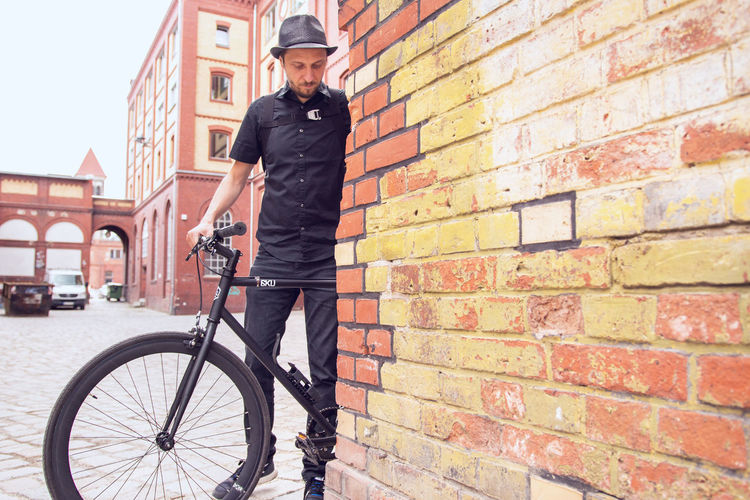 Brick Wall Hipster Style Old Brewery Wall Adult Architecture Bicycle Bicycling Bike Biker Brick Wall Building Exterior Casual Clothing City Cycling Full Length Guy Hipster Hipster - Person Hipster Guy Lifestyles Men Mid Adult Old Buildings On A Wall