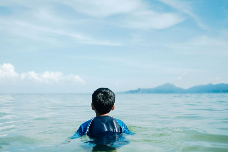 Rear view of boy in sea against sky