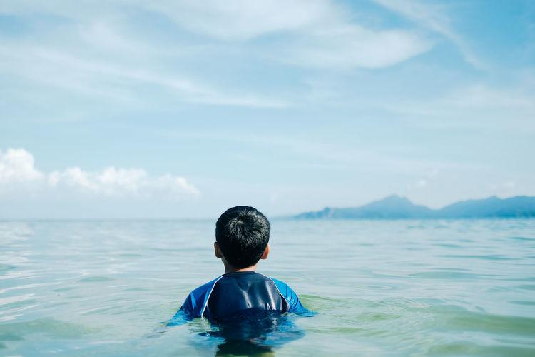 Rear view of boy in sea against sky