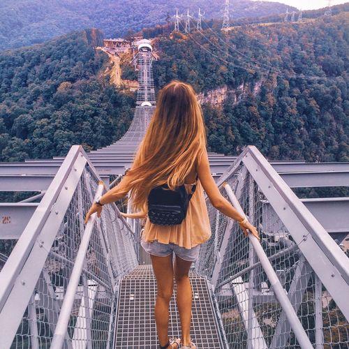 Rear view of woman standing on metal bridge