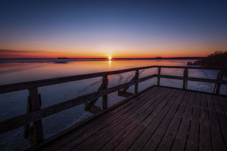View platform at Steinhude lake Water Sky Sunset Scenics - Nature Tranquility Tranquil Scene Wood - Material Sea Beauty In Nature Nature Reflection Railing No People Pier Boardwalk Beach Dusk Outdoors Wood Paneling Sunrise Steinhuder Meer Railing EyeEmNewHere Horizon Over Water Blue Sky