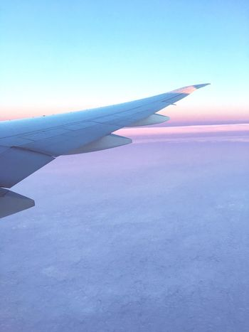 Sunset view of beautiful clouds and the tip of an airplane wing while flying in the plane Airplane Sunset