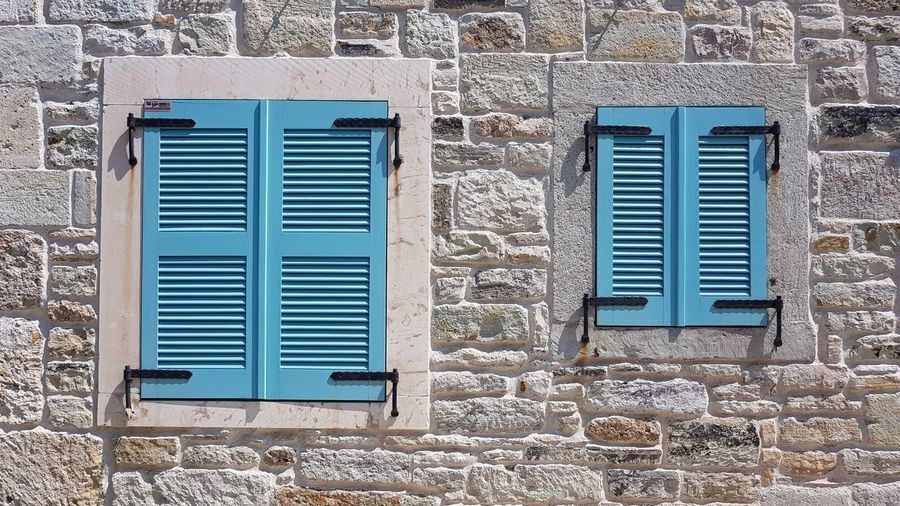 Foça, Turkey Shutters Turkey Architecture Blue Brick Brick Wall Building Building Exterior Built Structure Closed Day Foça Turkey House No People Old Outdoors Protection Residential District Safety Security Stone Wall Wall Wall - Building Feature Window Window Frame