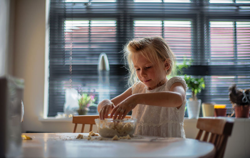 Girl making food on table at home