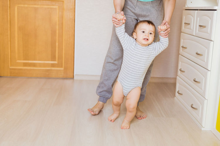 Low section of mother with baby standing on floor at home