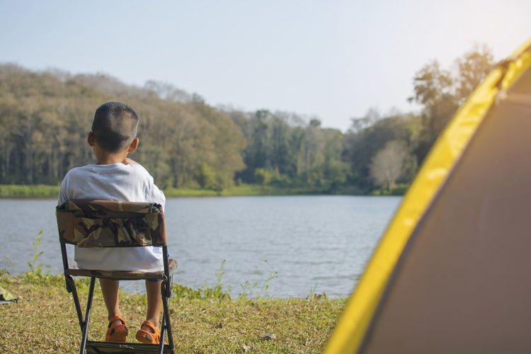 Back view of Asian child boy sitting on a chair for relaxing on camping in the tent with blur water resource and forest background Asian  Child Boy Sitting Chair Relaxing Camping Camp Tent Blurred Water Resource  Nature Forest Cute Green Activity Learning Education Outdoor Enjoyment Enjoy Kid Equipment Recreation  Happiness Vacation Tourist Travel Trip Explored Explore Real People One Person Lake Sitting Plant Day Lifestyles Beauty In Nature Looking At View Outdoors