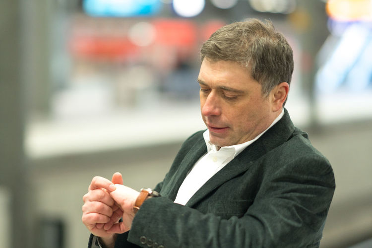 Thoughtful businessman checking time standing at railroad station platform