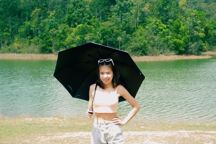 Portrait of smiling young woman standing on water