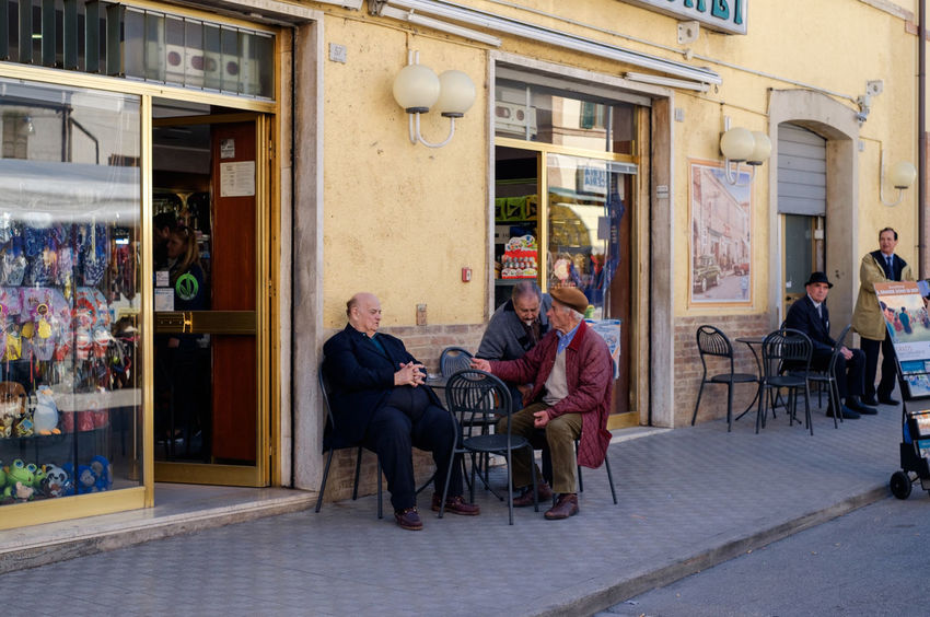 local cafe in Italy Adult Architecture Building Exterior Built Structure Cafe Chair City Day Full Length Group Of People Leisure Activity Lifestyles Men Outdoors People Real People Seat Sitting Table Women