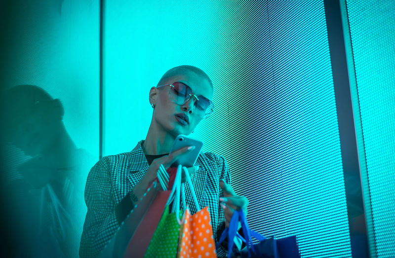 Low angle view of lesbian woman using smart phone holding shopping bags standing against abstract backgrounds
