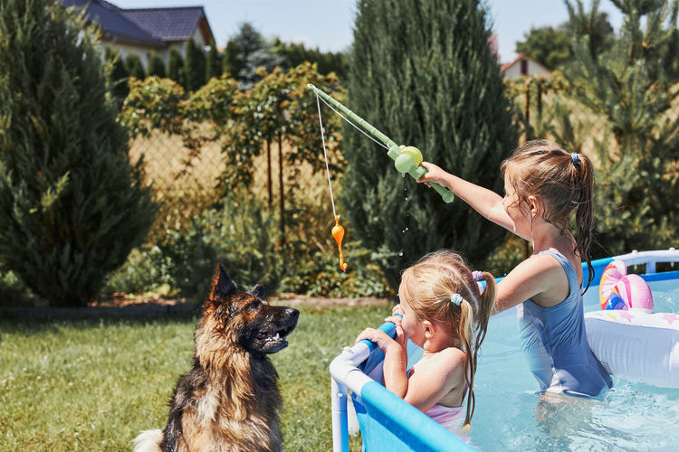 Children playing with dog using a fishing rod toy standing in a pool in a home garden