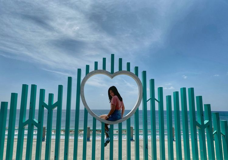 Woman sitting on heart shaped fence at beach against sky