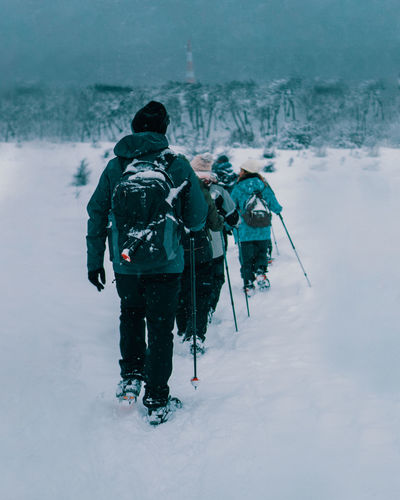 Rear view of people walking on snow