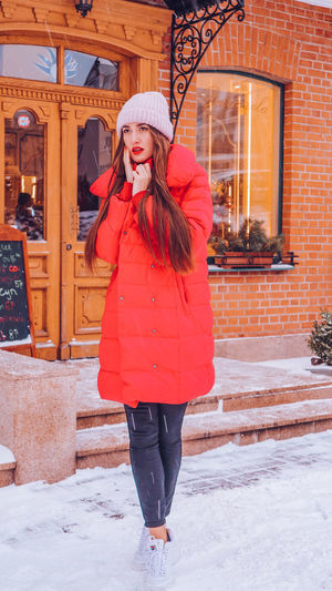Beautiful happy smiling woman on the street in warm red winter coat on Christmas time on snowing. Winter Cold Temperature Warm Clothing Snowing Smiling Christmas Wintertime Woman Power women around the world EyeEm Best Shots EyeEm Colorful! Fashion Stories Red Lipstick One Person Clothing Snow Real People Standing Young Adult Young Women Full Length Architecture Women Leisure Activity Lifestyles Front View Built Structure Beautiful Woman Hairstyle Outdoors Scarf