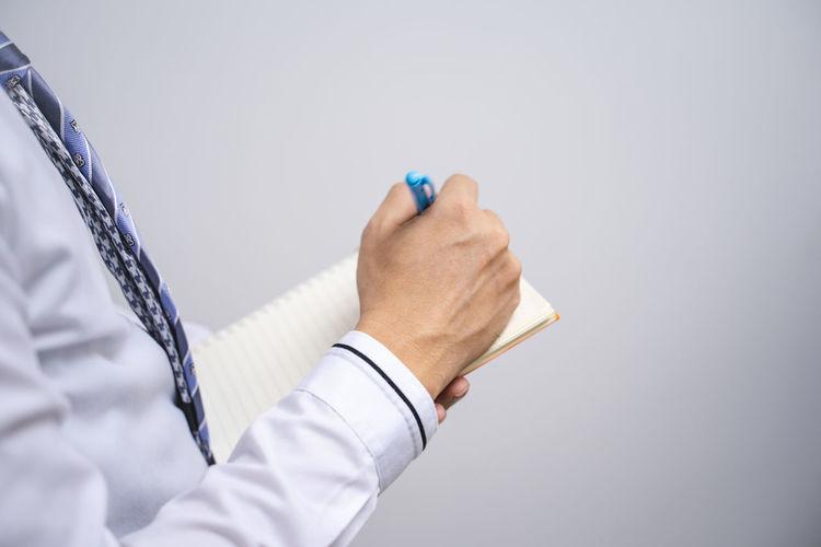 Close-up of man holding umbrella against white background