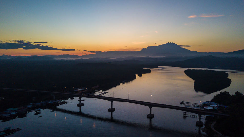 A beautiful sunrise captured using drone with silhoutte of a bride and mountain Beauty In Nature Day DJI Mavic Pro Dronephotography Gayang Bridge High Angle View Mengkabong River Mount Kinabalu Mountain No People Outdoors Reflection Sabah Borneo Scenics Silhouette Sky Sunrise Tranquil Scene Travel Destinations Tuaran, Sabah Water