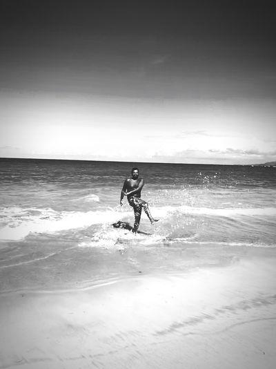 Shirtless man enjoying at beach against sky
