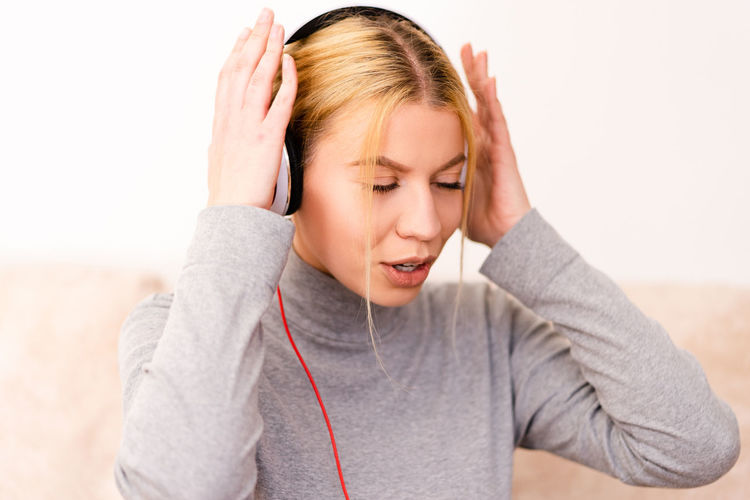 One Person Young Adult Headphones Portrait Blond Hair Music Young Women Emotion Listening Focus On Foreground Indoors  Headshot Women Casual Clothing Hair Adult Front View Lifestyles Hand Beautiful Woman Mouth Open
