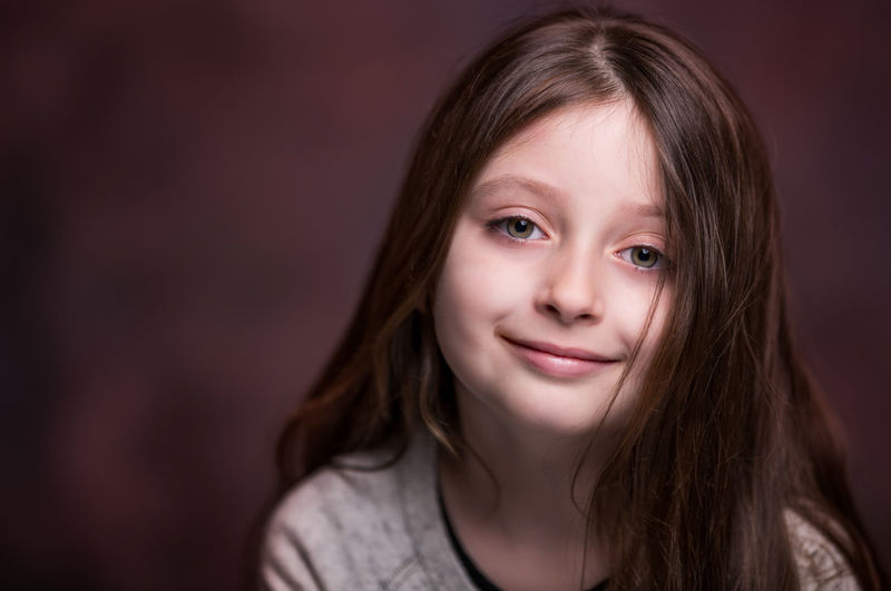 Close-up portrait of girl against brown background