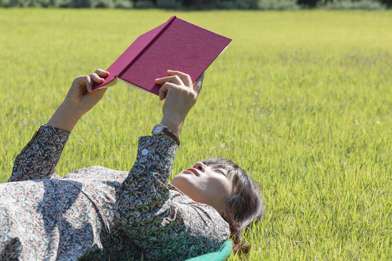 Full length of woman reading book on field