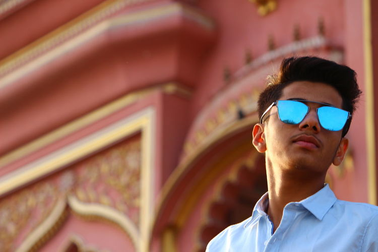 Low angle view of young man wearing sunglasses standing against building
