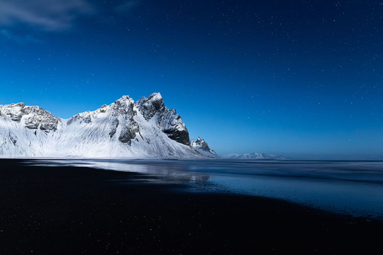 Snowy peaks lit by full moon light on a lonely calm clear blue night at stokksnes beach in iceland