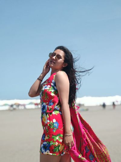 Side View Of Young Woman Standing At Beach Against Clear Sky During Sunny Day
