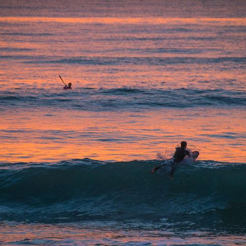 People enjoying in sea during sunset