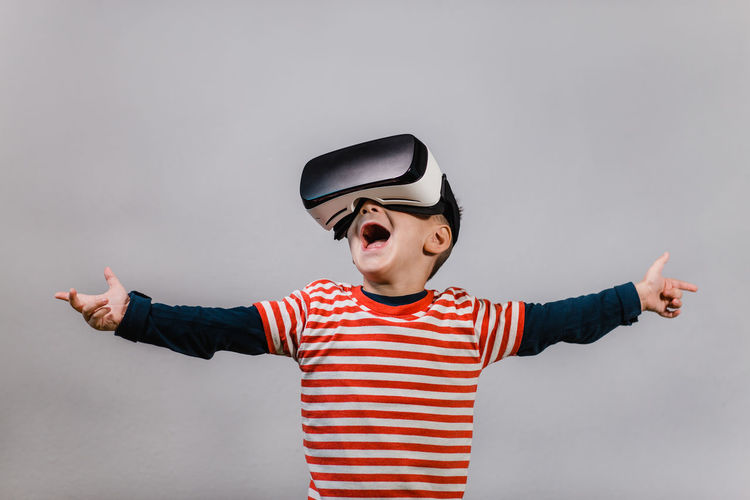 Portrait of happy child wearing virtual reality headset against grey background. Excited kid with hands spread having fun with VR glasses. Child Front View Striped Mouth Open One Person Indoors  Vr Virtual Reality Portrait Boy Red Color Headset Glasses Caucasian Technology Preschool Isolated Gadget Digital E-learning 3D Horizontal Education Hands Spread Having Fun