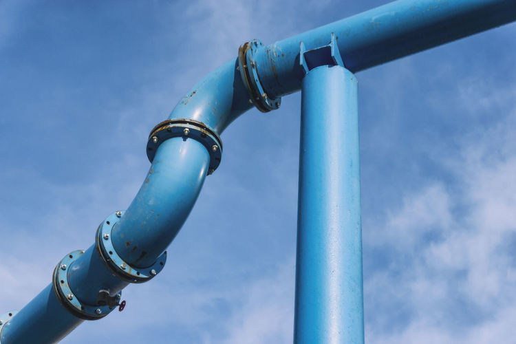 Low angle view of metallic pipe against sky