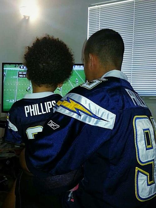 Casual Clothing Rear View Indoors  This Week On Eyeem Bonding Fatherhood Moments Family Togetherness Love Holding Indoors  Lifestyles Football Season Football Jersey Football Fans Tv Person Leisure Activity Happiness Loving Childhood Popular Affectionate