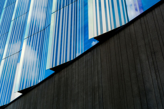 Abstract Architectural Feature Architecture Blue Blue Sky Building Built Structure City Cloud Day Directly Below Halved Low Angle View Minimalism Modern No People Office Building Outdoors Part Of Pattern Sky Stripes Pattern Tall - High