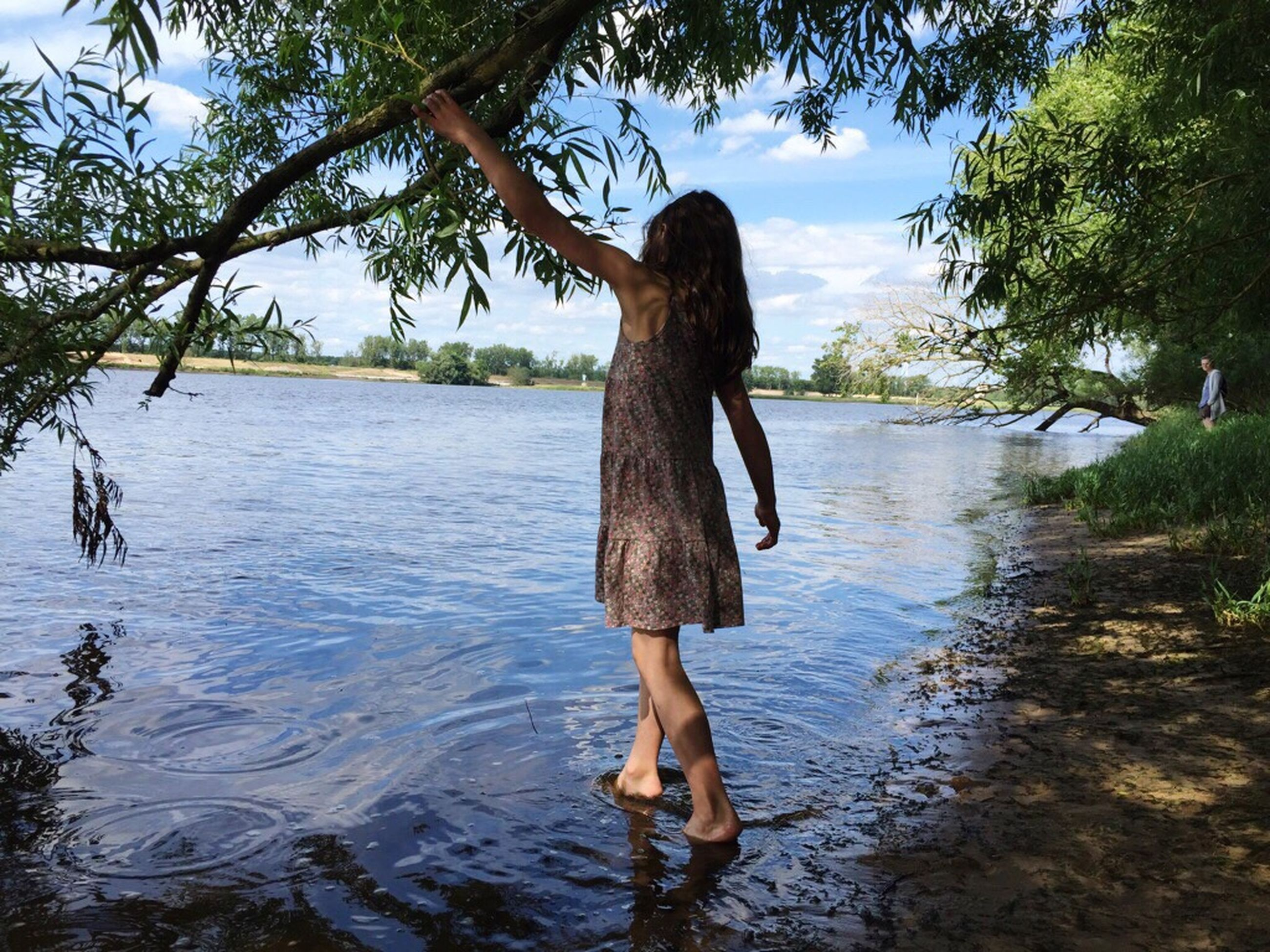water, tree, full length, lifestyles, leisure activity, standing, tranquility, sky, rear view, tranquil scene, nature, person, casual clothing, vacations, scenics, young adult, beauty in nature, day