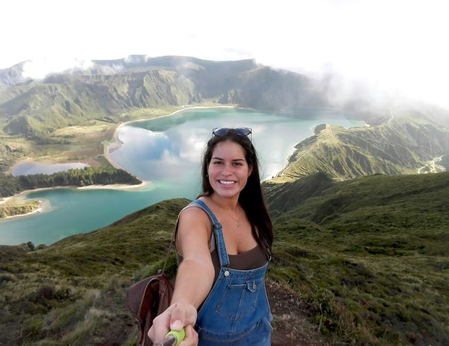 Portrait of smiling young woman standing at lake against sky