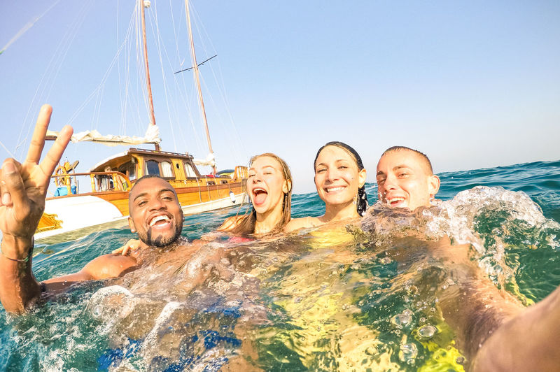 Portrait Of Cheerful Friends Swimming In Sea Against Clear Sky