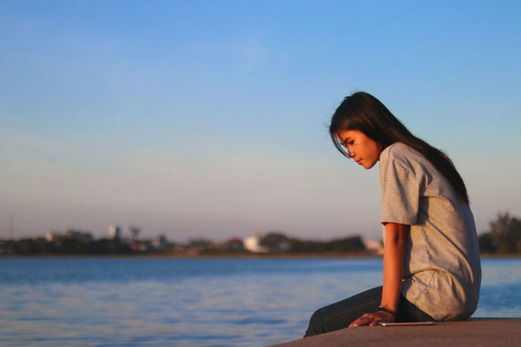 Side view of smiling young woman sitting on retaining wall by sea against clear sky during sunset