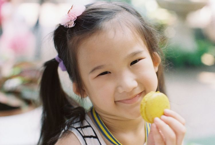 Close-up portrait of smiling girl holding macaroon