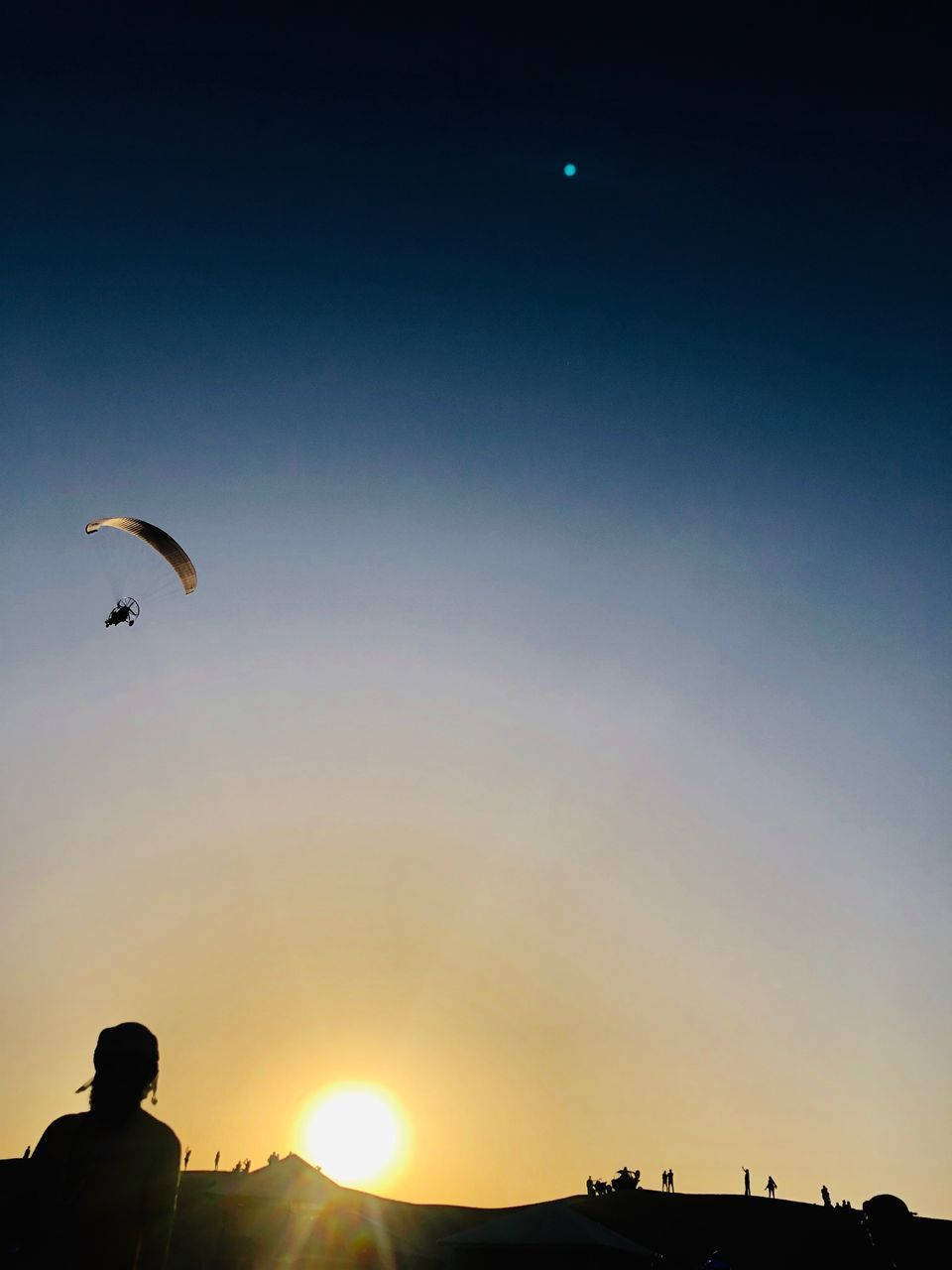 sky, real people, sunset, leisure activity, extreme sports, one person, lifestyles, parachute, silhouette, adventure, sport, flying, nature, mid-air, sun, paragliding, beauty in nature, unrecognizable person, copy space, outdoors, lens flare