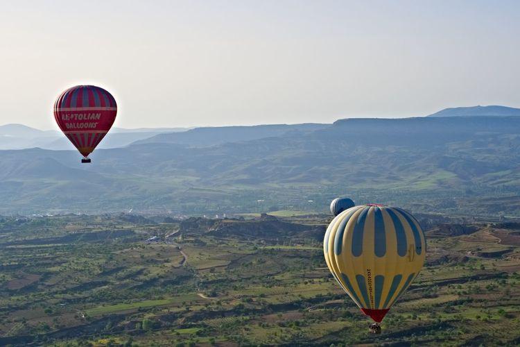 Hot air balloons Cappadocia Kapadokya Turkey Knycl EyeEm Selects Hot Air Balloon Air Vehicle Balloon Transportation Flying Mid-air Mountain Sky Adventure Nature Scenics - Nature Travel Landscape Ballooning Festival Clear Sky Travel Destinations
