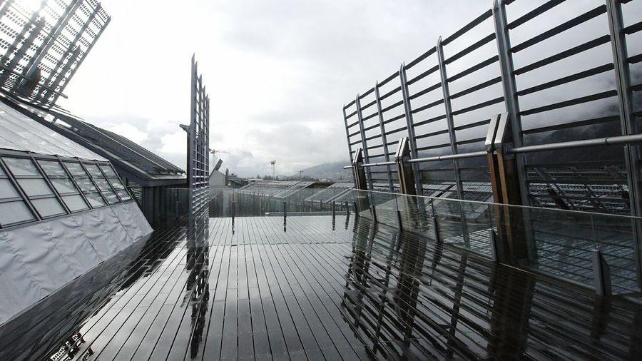Reflection of railings on wet boardwalk