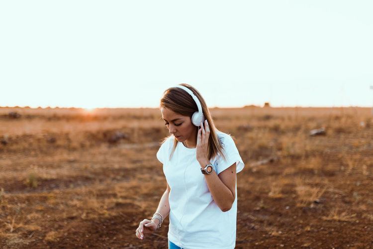 Young woman wearing headphones standing on field