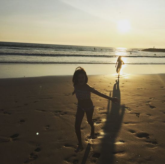 Full length of girls at beach against sky during sunset
