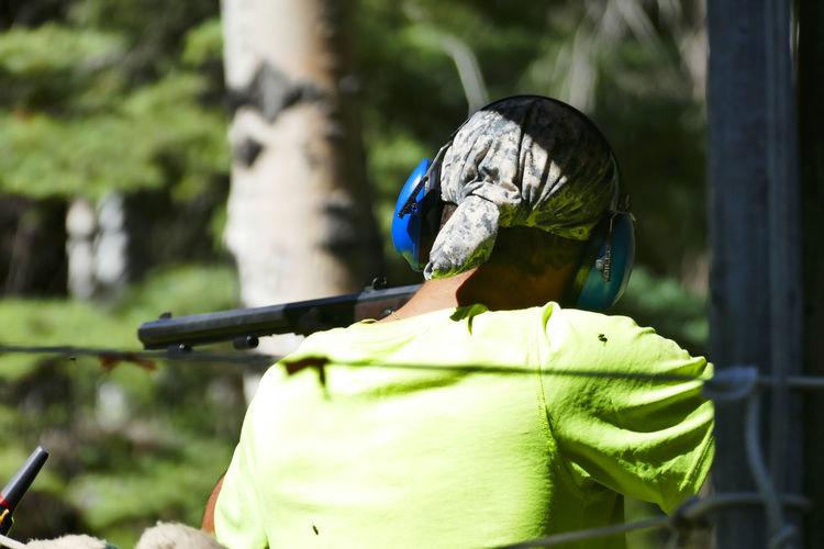 Rear View Of Man Shooting Gun