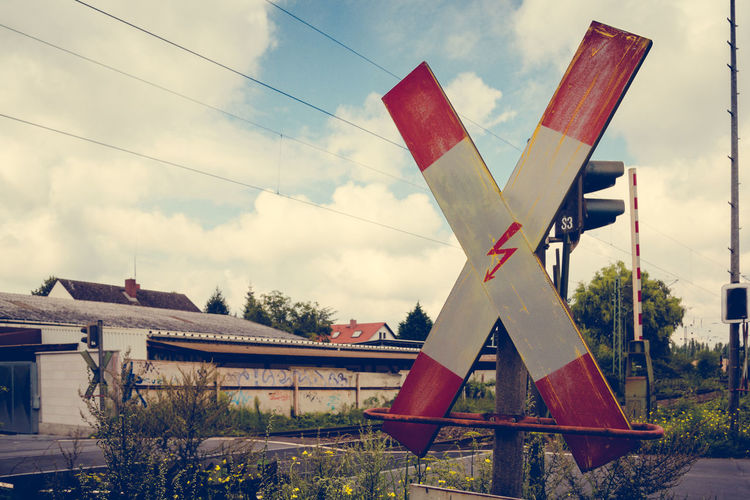 Railroad crossing sign against sky