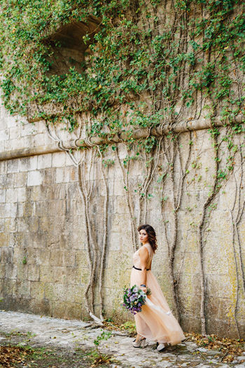 Full length of woman standing near wall