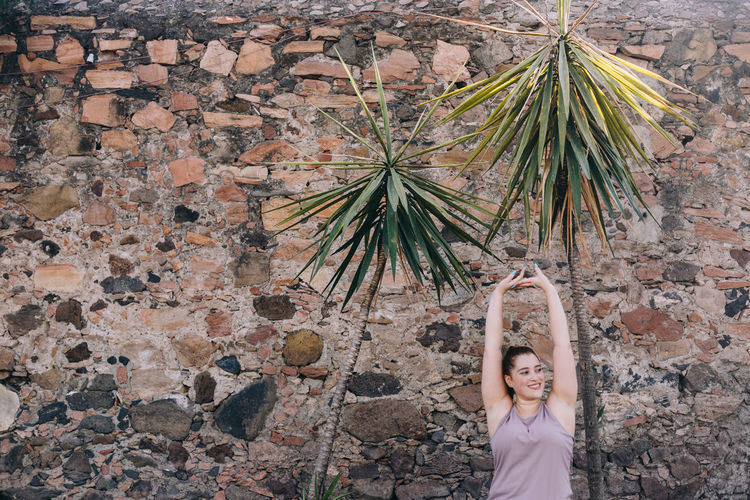 Portrait of woman standing against wall exercising