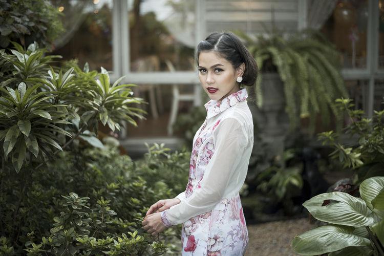 Portrait of beautiful woman touching plants in lawn