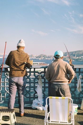Rear view of male friends fishing by sea against sky