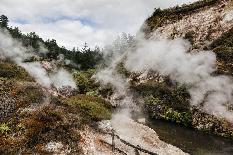 Smoke emitting from volcanic geyser against sky