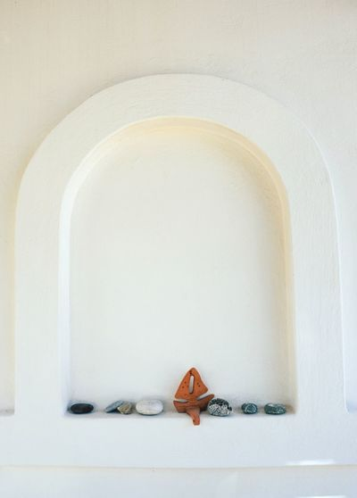 Pebbles And Model Boat In Niche Amidst White Wall